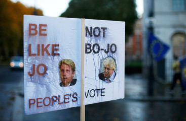 A rain damaged placard in favour of a second Brexit referendum features pictures of former Foreign Secretary Boris Johnson, and former Transport Minister Jo Johnson, in Westminster, London