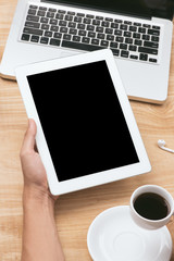 Mock up image of a hand holding black tablet pc with white blank screen and coffee cup on wooden table background