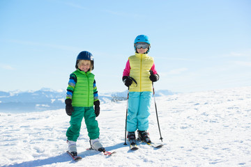 Smiling children skiing in the mountains during winter holiday