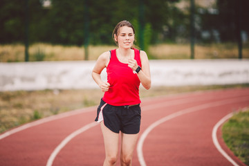 Beautiful young athlete Caucasian woman with big breasts in red T-shirt and short shorts jogging, running in the stadium with red rubber coating