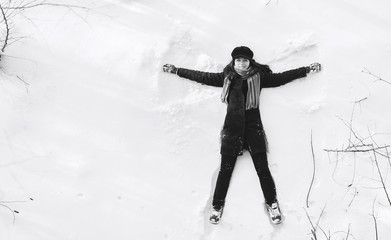 A girl on the snow shows an angel. Spreading arms. Top view. Drone. Smile. Happy. Black and white photography.