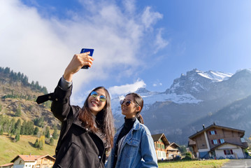 Selfie portrait of young best friends girls having fun together at kandersteg, Switzerland. Travel concept of happy girls make picture together and having fun, make funny faces on camera.
