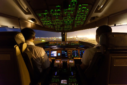 Inside cockpit on ground at an airport, both pilots are operating the airplane moving to the runway. Seen from observer behind pilots seat in the night time. Modern aviation concept.