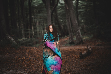 Man in blanket standing in forest