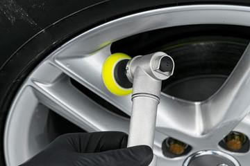 Car polish wax worker hands polishing wheel. Buffing and polishing car disk. Car detailing. Man holds a polisher in the hand and polishes the car. Tools for polishing
