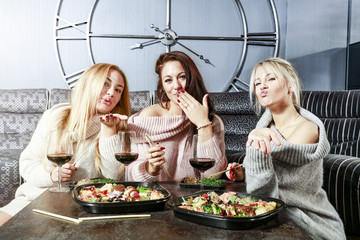 Three young women in sweaters. Sushi on the table and luxury home interior.