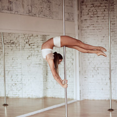 Obraz Stunning young slim woman in white clothes  performs pole dance and shows her fit figure in the studio - fototapety do salonu