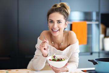 Beautiful Smiling Woman Eating Fresh Organic Vegetarian Salad In Modern Kitchen