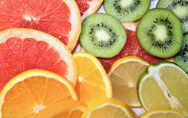 Various citrus and kiwis sliced into round slices on white background. The view from the top.