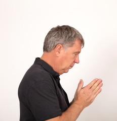 mature man in black  shirt praying