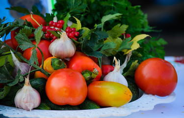 Fresh vegetables,red bell peppers, tomatoes, garlic, herbs and berries closeup on the plate on the table