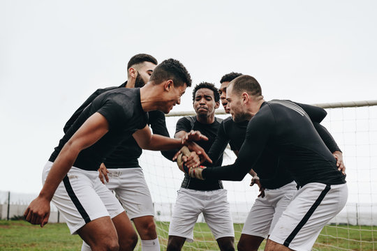 Soccer players joining hands standing in a huddle