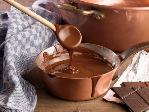 Melted chocolate in sauce pan with wooden spoon on table