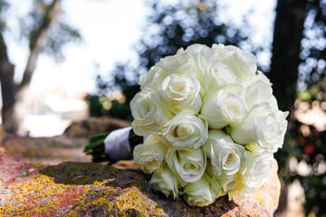 Bouquet di rose bianco poggiato su una roccia