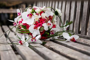 Bouquet di orchidee bianche e rosa poggiato in una panchina in legno