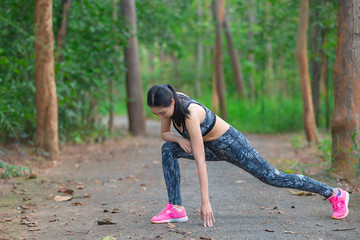 Asian sporty woman stretching body breathing fresh air in the park,Thailand people,Fitness and  exercise concept,Jogging in the park,Warm up body