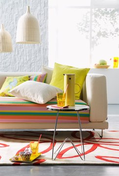 Sofa with striped upholstery and scatter cushions, small side table and wicker pendant lamps