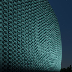 The facade of the building in modern style with night lighting. Concrete honeycomb modern facade. 3D