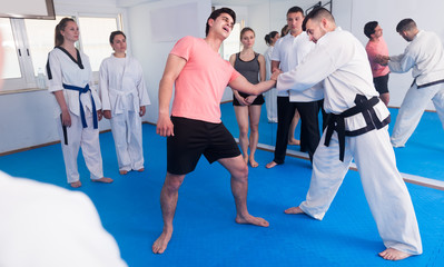 man training new taekwondo holds with adults during class