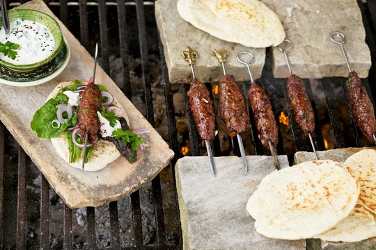 Shish kebabs with flatbread served on marble board