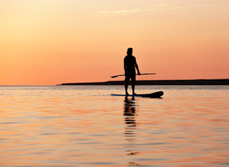 Silhouette of a beautiful woman on SUP surfing.