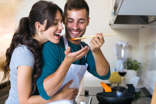 Handsome young man giving his wife to try the food he is preparing in the kitchen at home.