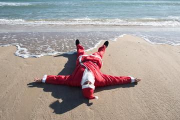 santa claus lying on the sand of a beach