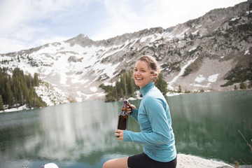 A woman opens a beer bottle at a mountain lake.