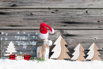 Tafel mit Text Frohe Weihnachten mit Rentier und Nikolausmütze rustikal vor Holzhintergrund als Kartenmotiv