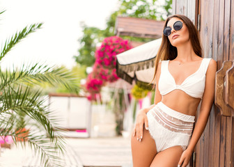 girl lies on a tropical beach on pink sun loungers