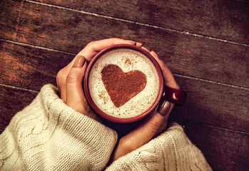 woman holding hot cup of coffee with heart shape symbol. Above view