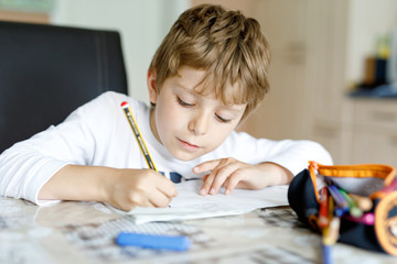 Tired little kid boy at home making homework at the morning before the school starts. Little child...