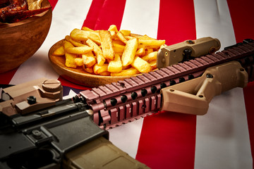 delicious fried chicken wings, french fries and rifle against USA flag background