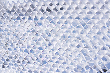 Metal mesh fence with mesh chain-link covered with snow. Texture in a cage.