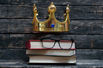 Premium books under a king crown. VIP high quality education concept. Knowledge is a power.