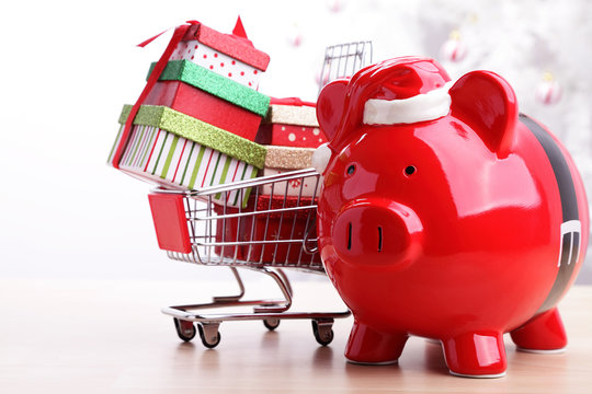 Christmas piggy bank next to a shopping cart full of presents