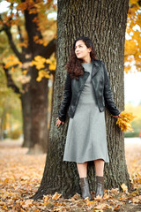Woman with yellow leaves stand near big tree in autumn city park.