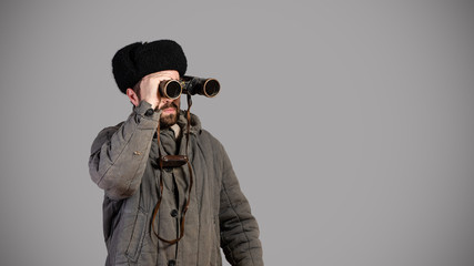 Soviet scout with binoculars keeps track of the situation, studio shot. Great Patriotic War theme