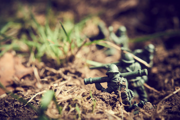 Soldiers in jungle fighting. Concept image of toy plastic soldiers in real grass.  Selective focus.