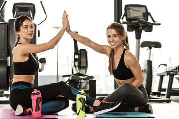 Two beautiful fitness girl cheering up each other and clapping their hands after successful workout at the gym