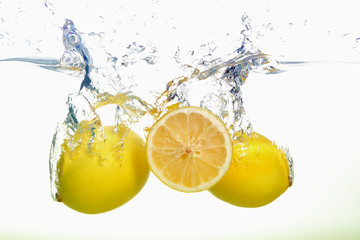 Two lemons and lemon slice spash in water on white background