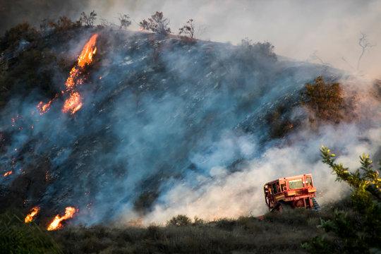 Bulldozer works on Burning Hillside During California Woolsey Brushire
