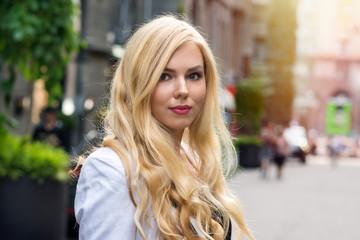 Beautiful young blond girl posing on street, closeup