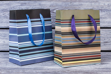 Two striped shopping bags on wooden background. Two paper bags with colorful stripes, horizontal image.