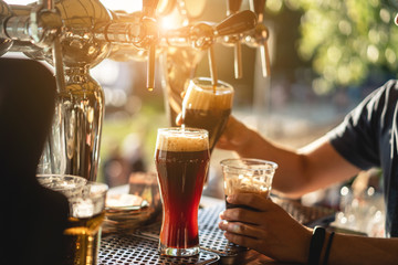 bartender pours a dark beer close up