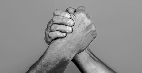 Man hand. Two men arm wrestling. Arms wrestling. Closep up. Friendly handshake, friends greeting, teamwork, friendship. Handshake, arms, friendship. Hand, rivalry, vs, challenge, strength comparison Wall mural