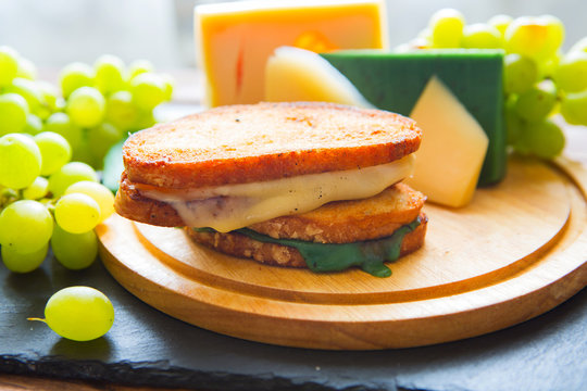 Two hot grilled or fried sandwich with cheese and green grapes on black slate cheeseboard on wooden table