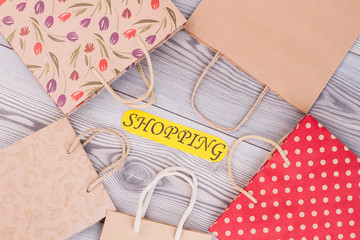Paper bags and card with inscription shopping. Set of kraft paper packets on wooden background. Holiday shopping concept.