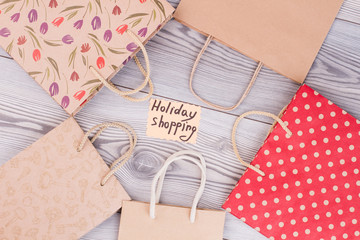 Group of shopping bags on wooden background. Collage from kraft paper carrier bags. Card with inscription holiday shopping.