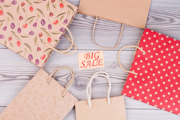 Big sale concept. Paper shopping bags and card with inscription big sale on wooden background, top view.
